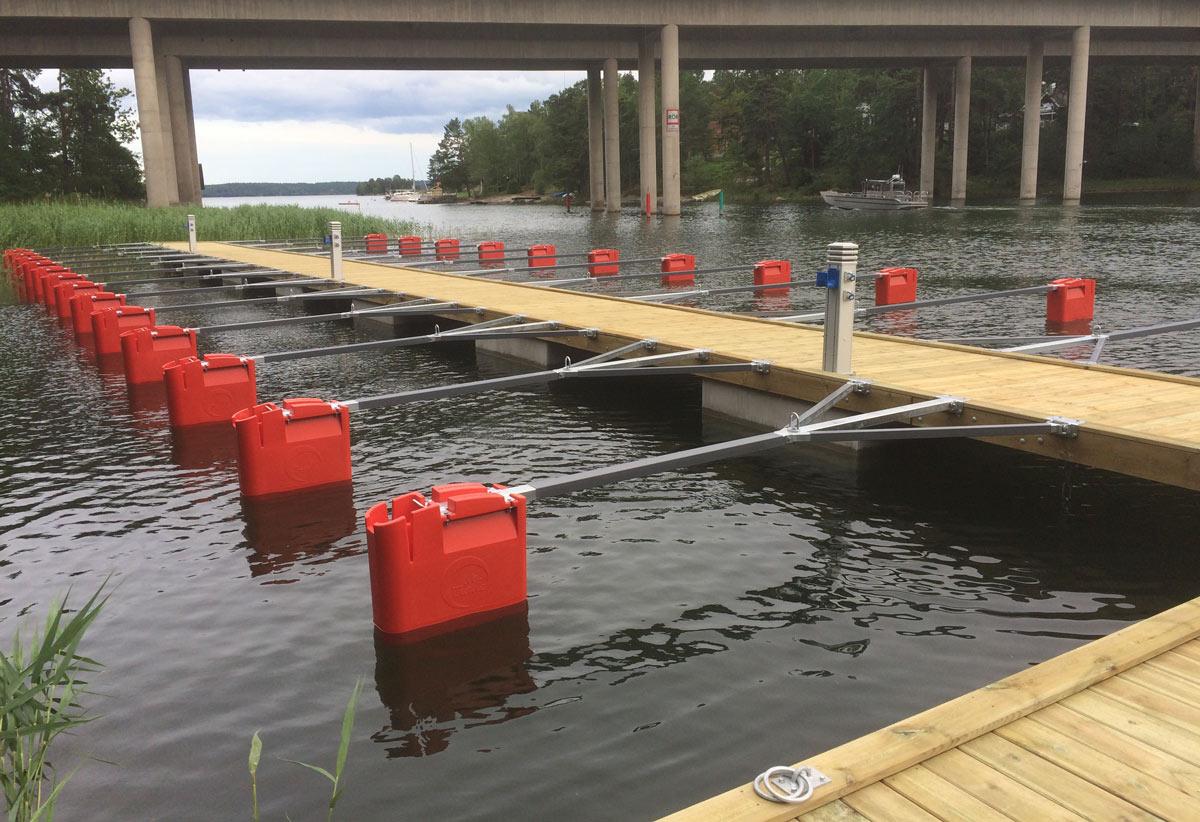 Trä-betongbrygga med Y-bommar förankrade i vattnet. En hög bro i bakgrunden.